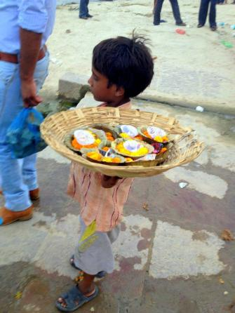 Small child selling marigold flowers along the Ganges at Varanasi.
