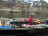 A man selling local provisions and trinkets from his floating boat store, on the Ganges river.