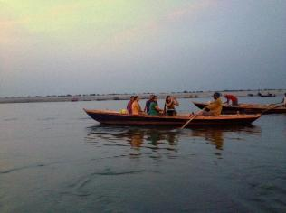Indians taking a sunrise boat ride along the Ganges.