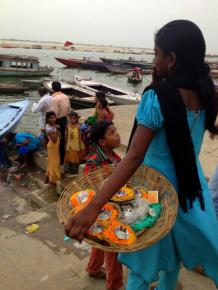 Selling marigold cups with candles in them to set free along the river during the Sunset Ceremony.