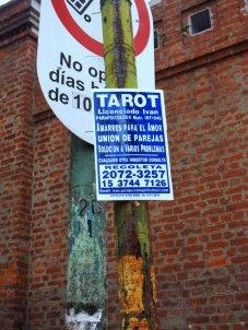 A tarot card reader's advert outside the cemetery walls.