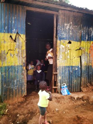 Primary school children peaking out of their classroom in Kibera.