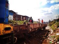 People riding the railway carts in Kibera.
