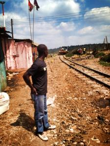 One of our guides standing along the railway which runs through the middle of Kibera.
