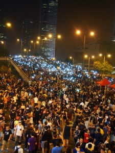 Protesters in the central business district of Hong Kong hold up cell phones with their lights illuminated in a show of solidarity.
